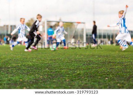 Shallow depth of field shot of young boys playing a kids football match on green turf. - stock photo