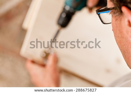 shallow depth of field with focus on the glasses of the carpenter using a drill driver on a component of a piece of furniture - stock photo