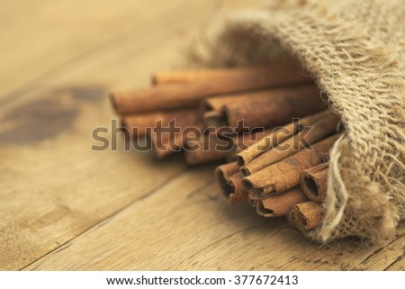Shallow DOF closeup of cinnamon barks in burlap sack over rustic wooden table - stock photo