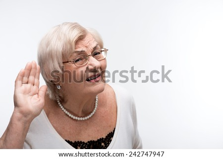 Shameless eavesdropper. Portrait of curious elderly woman holding hand by her ear and struggling to hear something while standing over white background - stock photo