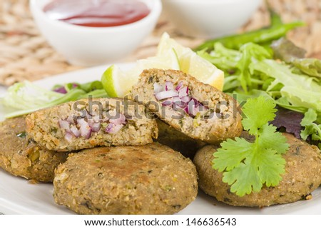 Shami Kebab - Minced meat and chana dal patties stuffed with red onion pickle and served with salad, lemon wedges, chilli sauce and mint raita, South Asian & Middle Eastern cuisine. - stock photo