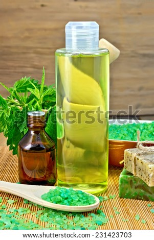 Shampoo, oil, gel, salt, soap with nettles in a mortar on a wooden boards background - stock photo