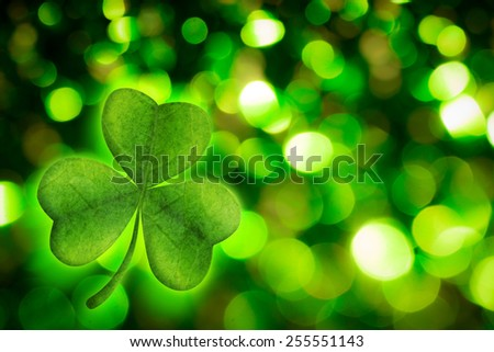 Shamrock against green glowing background - stock photo