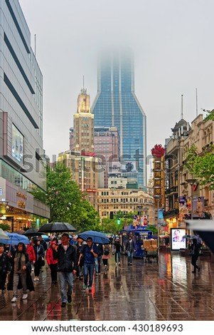 SHANGHAI, CHINA - April 20, 2016: Rainy day at Nanjing Road in Shanghai. The wettest weather in Shanghai is in September and the driest weather is in December - stock photo
