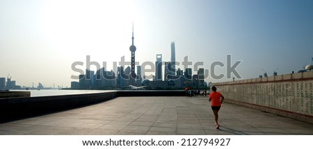 Shanghai, China - August 6, 2014: A beautiful view of Shanghai Skyline at sunrise with people running. - stock photo