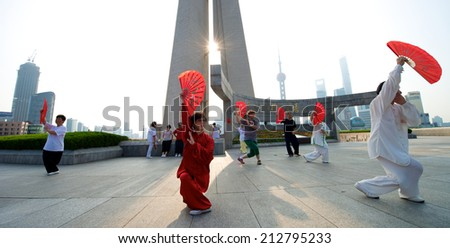 Shanghai, China - August 6, 2014: A beautiful view of Shanghai Skyline at sunrise with people doing Tai Chi.  - stock photo