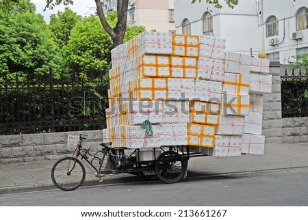 SHANGHAI, CHINA-AUGUST 19, 2013: typical tricycle transport. The largest Chinese city by population has thousand of these transports. - stock photo