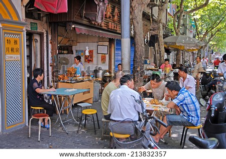 SHANGHAI, CHINA-AUGUST 24, 2013: Yangpu  area, locals dining in a  typical restaurant. Life example in the largest Chinese city by population. - stock photo