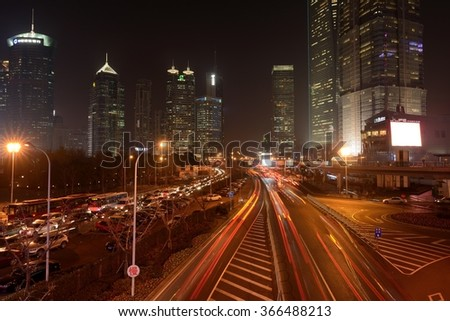 Shanghai, China - December 23, 2014: In Lujiazui Pudong New Area, as night comes, all its skyscrapers and big buildings lit up, and the streets are filled with heavy traffics. - stock photo