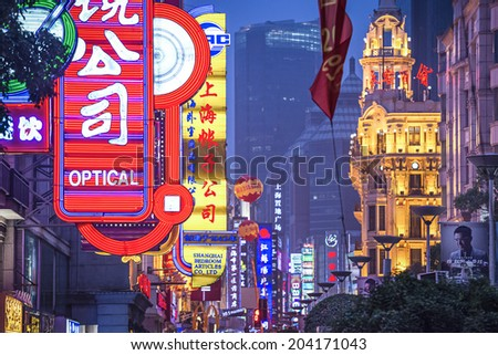 SHANGHAI, CHINA - JUNE 16, 2014: Neon signs lit on Nanjing Road. The street is the main shopping road of the city. - stock photo