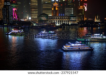 SHANGHAI, CHINA - NOV 23, 2014: The tour boats that cruise the Huangpu River of Shanghai are a popular tourist attraction as the skyline is magnificent at night. - stock photo