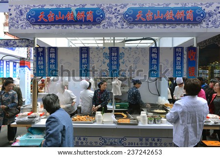 SHANGHAI, CHINA - NOV 13, 2014: Unidentified employees prepare food at a popular food kiosk in the busy Chenghuang Miao area in the Old City of Shanghai. - stock photo
