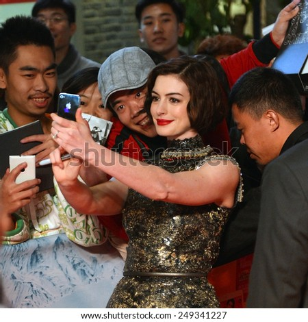 SHANGHAI, CHINA - NOVEMBER 10, 2014: Anne Hathaway poses for selfie with happy fans at the movie premiere of Interstellar at UME Theater in Shanghai, China - stock photo