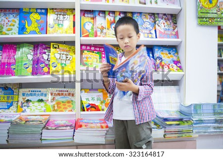 Shanghai,China-October 1,2015:Asian boy reading book at library,Shanghai - stock photo