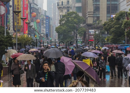 SHANGHAI, CHINA - 28th MARCH 2014: Nanjing road, a shopping mecca doesn't even stop for the rain. - stock photo