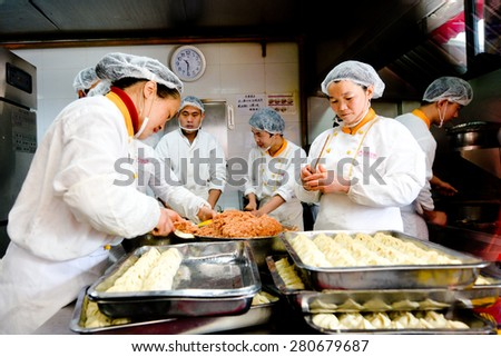 SHANGHAI, CN - MAR 17 2015:Chines chefs prepare Dim sum dumplings food at Yuyuan Tourist Mart in Shanghai, China.Dim sum dumplings it's the most popular and famous food in Shanghai, China - stock photo