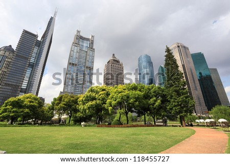 shanghai greenbelt park with modern building in cloudy - stock photo