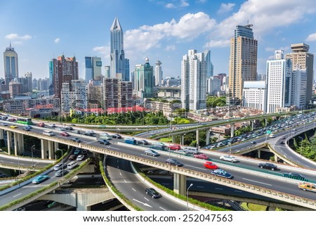 shanghai highway overpass with modern city skyline against a sunny sky - stock photo
