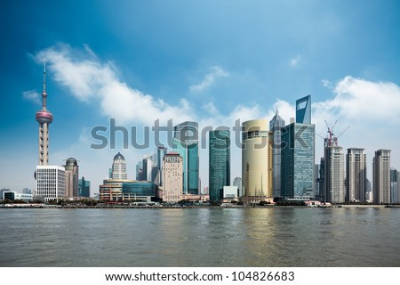 shanghai lujiazui financial center with huangpu river against a blue sky - stock photo