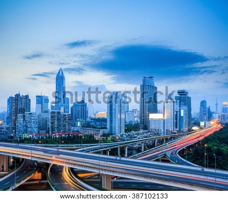 shanghai modern skyline with city interchange overpass in night falls - stock photo