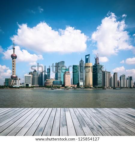 shanghai skyline against a blue sky with wooden floor - stock photo