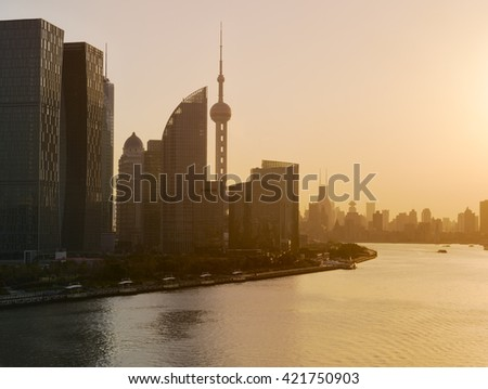 Shanghai skyline and Huangpu river in a beautiful dusk scene with sunset glow - stock photo