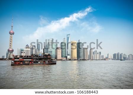 shanghai skyline and pleasure boat on the huangpu river - stock photo