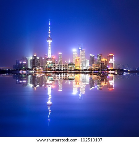 shanghai skyline at night,and reflection in the huangpu river - stock photo
