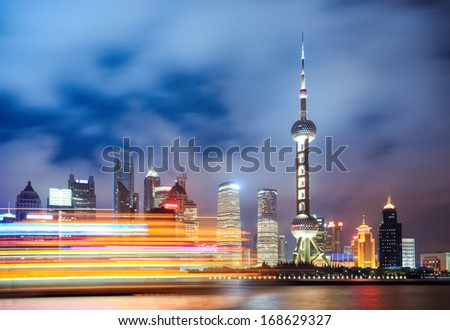 shanghai skyline at night with light trails of a cruise ship,China - stock photo