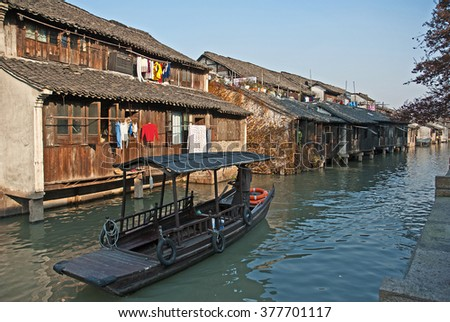 Shanghai, Wuzhen historic scenic town old houses and boat for tourists along a canal.  - stock photo