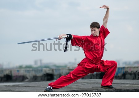 Shaolin warriors wushoo man in red with sword practice martial art outdoor. Kung fu - stock photo