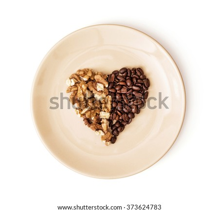 Shape heart of coffee beans and peeled walnuts on the plate. Valentine's Day. Symbol of love. - stock photo