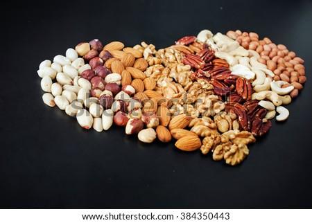 Shape Heart Peanut Almond Cashew Walnut Hazel Nut Pecan Black Wooden Background Top view Healthy Concept - stock photo