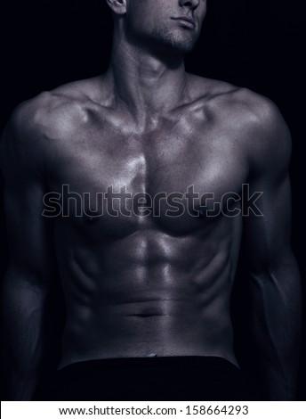 shape of sporty male body on dark - stock photo
