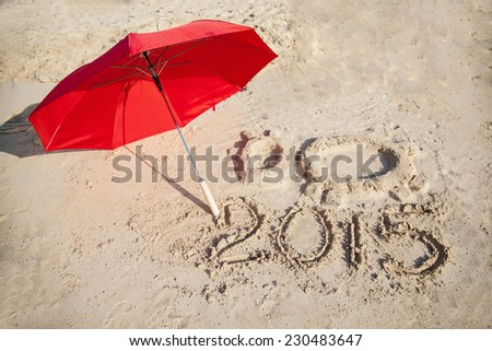 Shape of the Goat (symbol of 2015 year), red umbrella and 2015 number on sandy Cyprus beach - stock photo