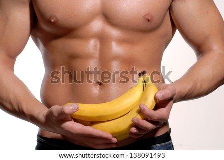 Shaped and healthy body man holding a fresh bananas,shaped abdominal, - stock photo