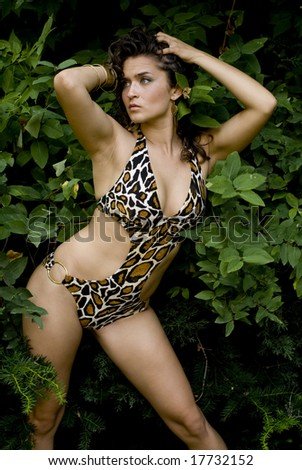 Shapely female posing in leopard print swimsuit with trees behind her - stock photo