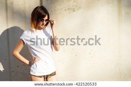 Shapely young girl wearing in a white blank t-shirt and sunglasses posing against a background of a concrete wall in the rays of the setting sun - stock photo