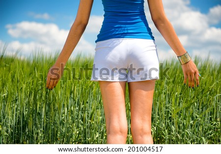 Shapely young woman in shorts enjoying a day in nature standing with her back to the camera looking out over a green field under a sunny blue cloudy summer sky - stock photo