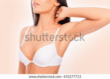 shapely young woman with perfect body with the drawing arrows wearing white bra, touching her neck - stock photo