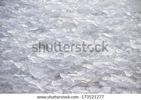 Shards of ice are tossed onto the shoreline of Lake Michigan by strong winter wave action. - stock photo