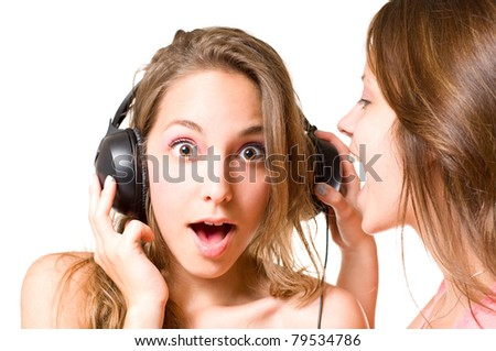 Share your music, brunette girl shouting to one wearing headphones, shocked expression. - stock photo