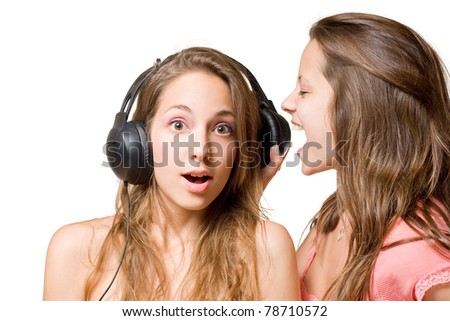 Share your music, two beautiful young brunette girls fighting over headphones, isolated on white background. - stock photo