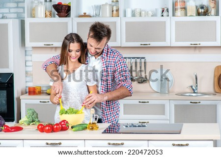 Shared cooking. Young and beautiful loving couple and help each other while cooking dinner with vegetables in the kitchen. - stock photo