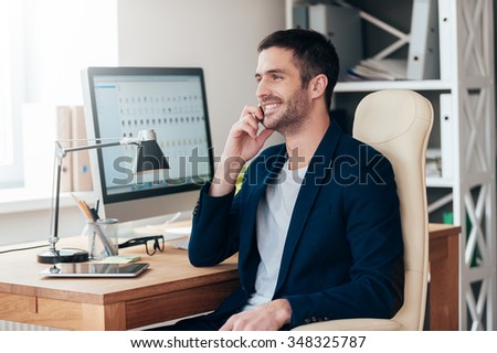 Sharing good news. Side view of handsome young man talking on the mobile phone and smiling while sitting at his working place in office - stock photo