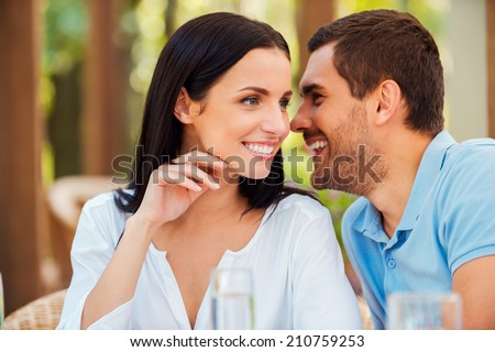 Sharing secrets with her. Handsome young man telling something to his girlfriend and smiling while sitting at the table outdoors together - stock photo