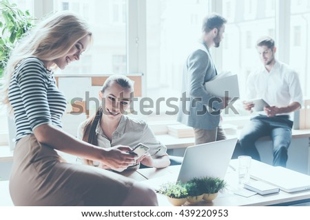 Sharing the latest news. Two beautiful young businesswomen discussing something and smiling while sitting in office with colleagues standing in the background  - stock photo