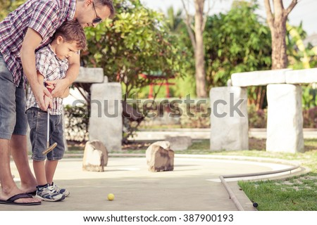 Sharing with golf experience. Cheerful young man teaching his son to play mini golf at the day time.  Concept of friendly family. - stock photo