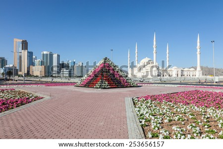 SHARJAH, UAE - DEC 17: Flower pyramid and the Grand Mosque in the city of Fujairah. December 17, 2014 in Fujairah, United Arab Emirates - stock photo