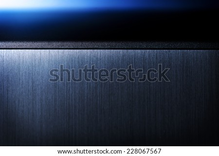 Sharp edged brushed metal and blue light background.?Shallow depth of field. - stock photo